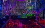 Red, purple and green light shine in the laboratory equipment used to create atomic gases for experiments.